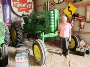 Eunice Bosomworth stands beside a JD Hi-Crop