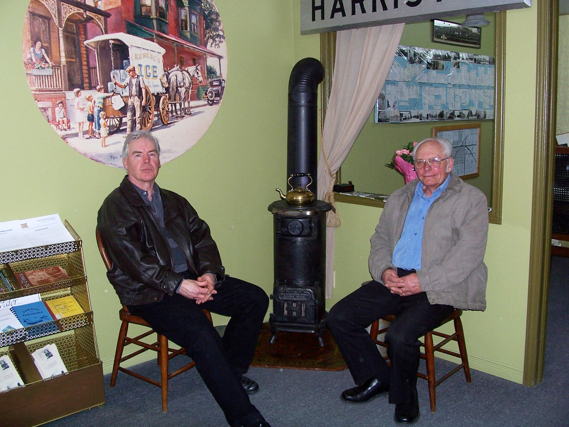 """Kim MacKenzie, left and Roy Charters relax in the """"Hot Stove Lounge"""" at the new Harriston Historical Society headquarters.  Willa Wick photo"""
