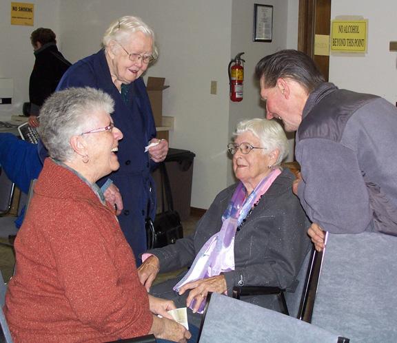 Morris Langwisch shares a story with (left) Mable Williamson, Marion Bracken, and Shirley MacKenzie