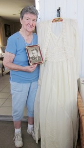 91-year old Phyllis Mason displaying her parachute wedding dress and army portrait of her husband.