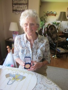 Theresa Beute holds the commerative medal they received at the Ex in 3013