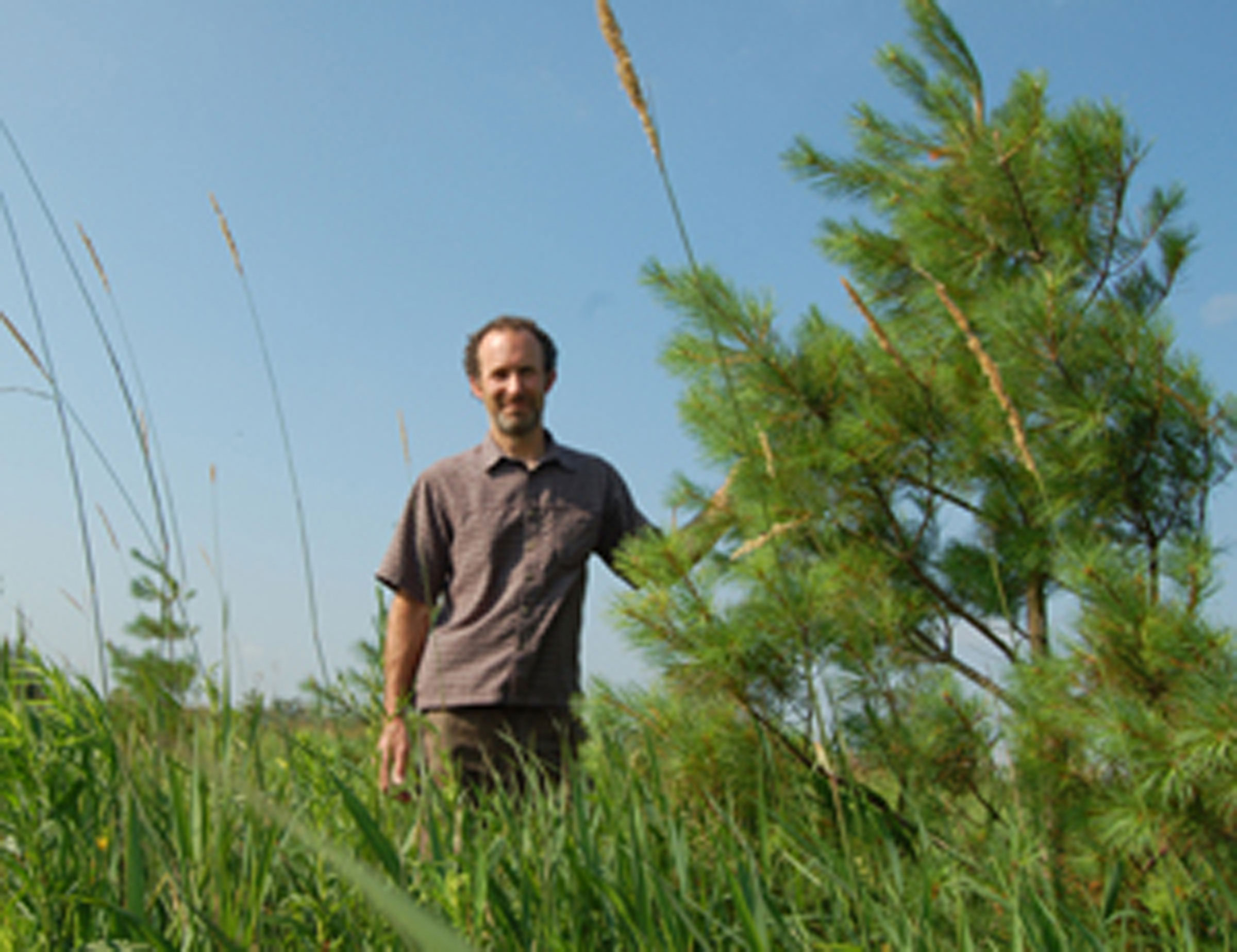 Jim Phillips stands by a tree in a field on his property. GRCA photo