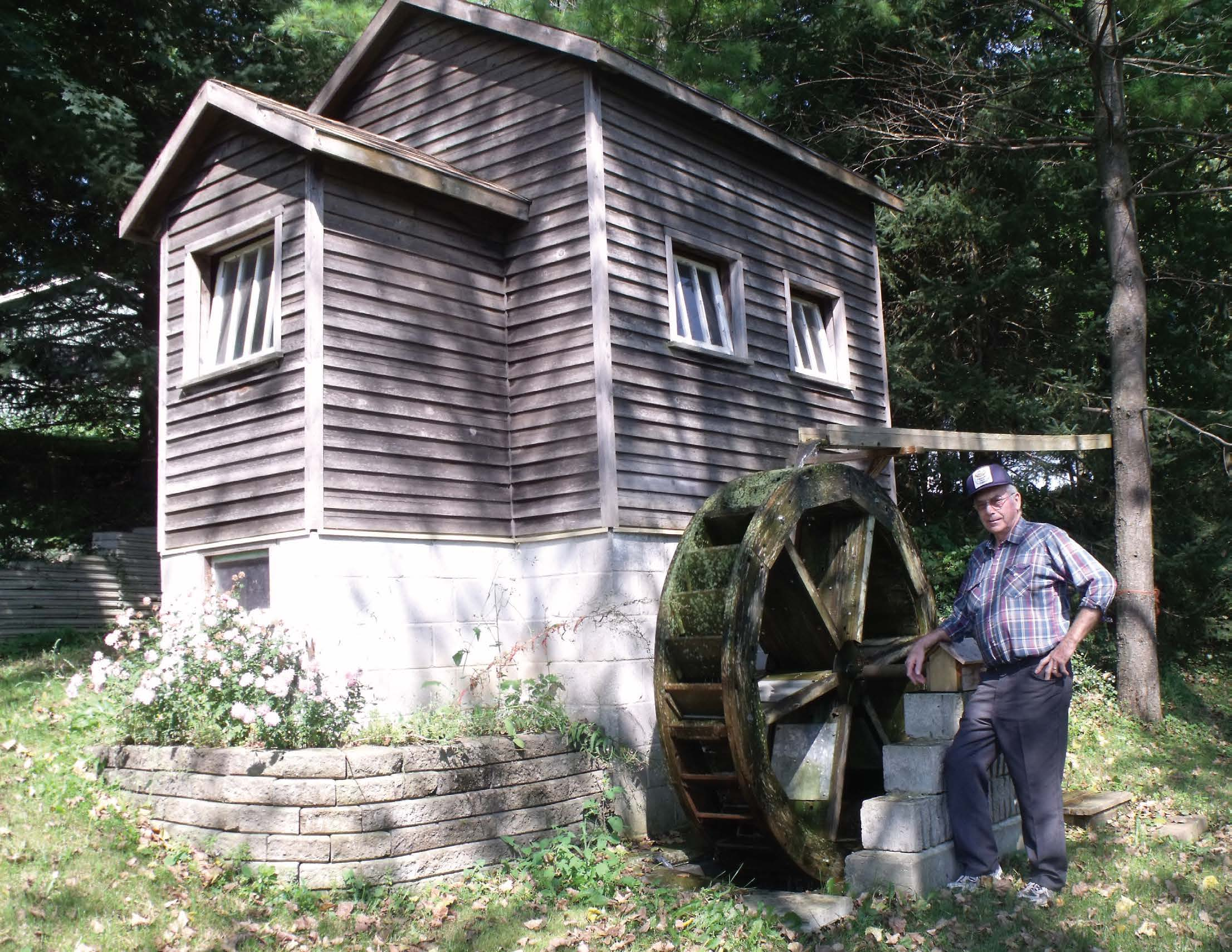 Floyd Schieck stands beside the working grist mill he built in the backyard of his Drayton home. Patrick Raftis photo