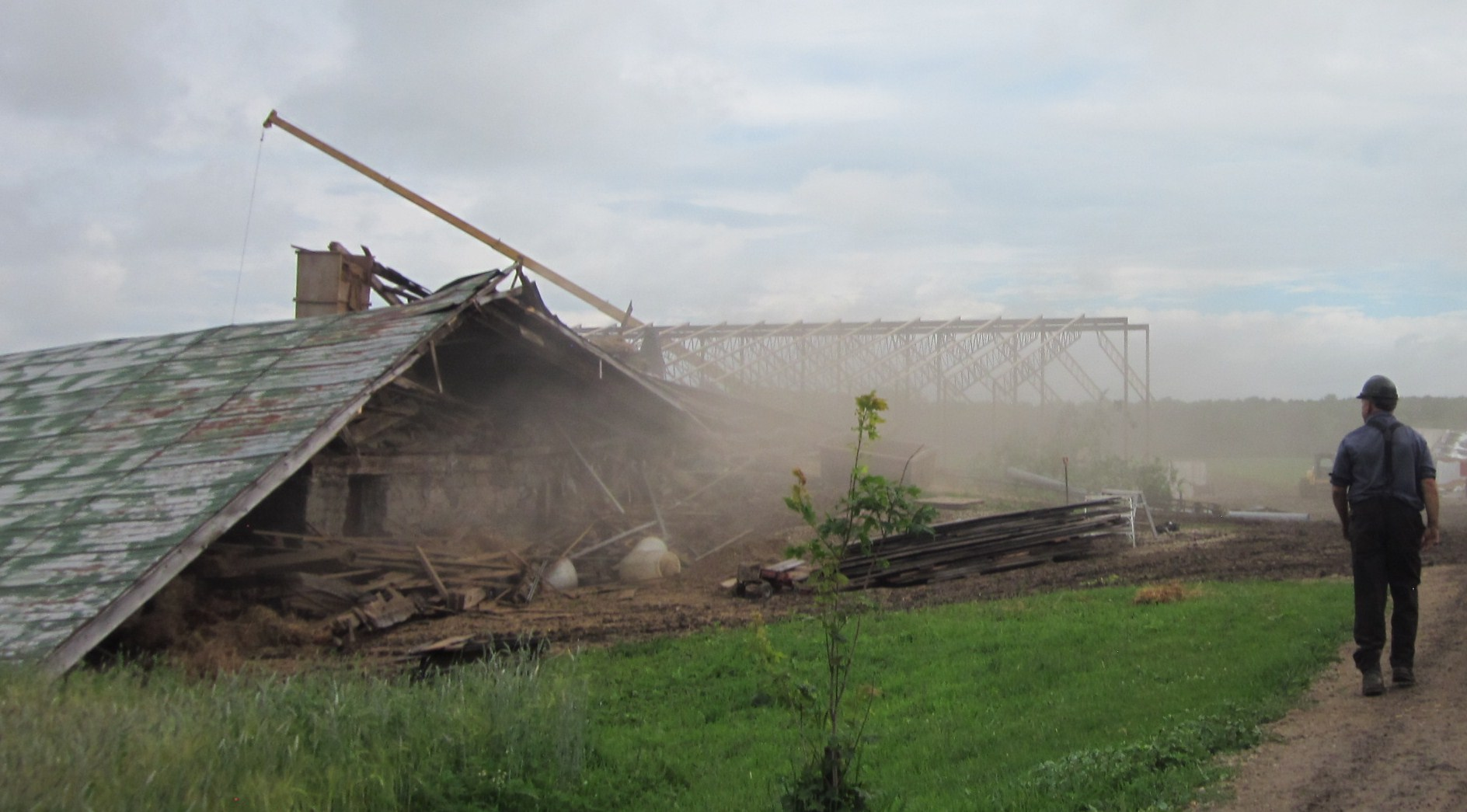 The old bank barn lies in a pile of dust while the frame of the new steel barn is almost completed (Willa Wick photo)