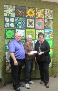 2016 IPM Quilt Committee Chair Renske Helmuth (centre) presents Anne and Earl Schneider (IPM hosts) with the first raffle ticket (Willa Wick photo)