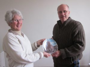 Director Willa Wick, on behalf of the Wellington County Historical Society, presents a vintage plate to new owner of the Post Office, Michael Hendrick
